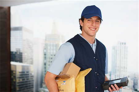Deliveryman carrying packages and electronic device Stock Photo - Premium Royalty-Free, Code: 635-05651548