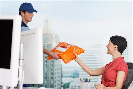 supply - Deliveryman handing package to businesswoman Stock Photo - Premium Royalty-Free, Code: 635-05651558