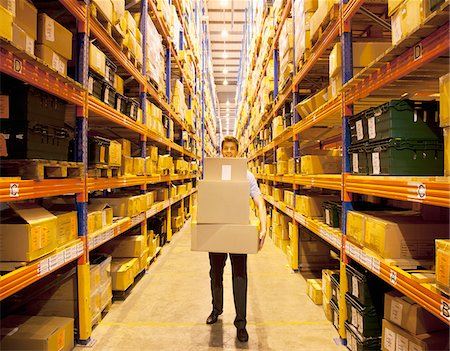 piles of work - Worker carrying boxes in warehouse Stock Photo - Premium Royalty-Free, Code: 635-05651559