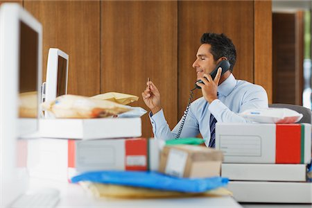 piles of work - Businessman talking on telephone behind packages Stock Photo - Premium Royalty-Free, Code: 635-05651553