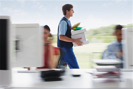 supply - Deliveryman walking with packages in office Stock Photo - Premium Royalty-Free, Code: 635-05651569