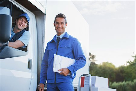 Worker standing outdoors with delivery driver Stock Photo - Premium Royalty-Free, Code: 635-05651561