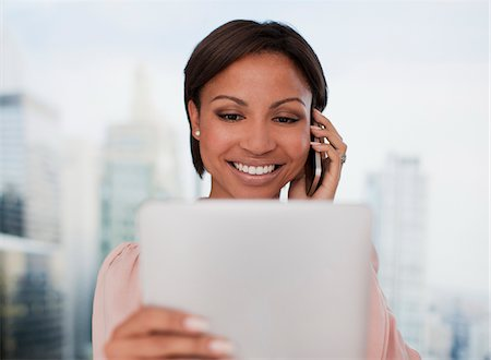 Businesswoman holding digital tablet and talking on cell phone Stock Photo - Premium Royalty-Free, Code: 635-05651574
