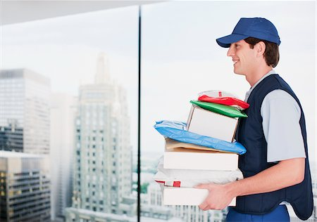 piles of work - Deliveryman carrying stack of packages Stock Photo - Premium Royalty-Free, Code: 635-05651577