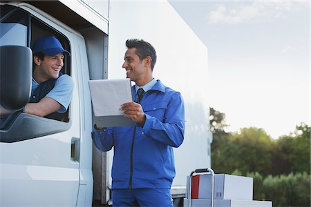 dependable - Deliveryman talking with worker holding clipboard Stock Photo - Premium Royalty-Free, Code: 635-05651584