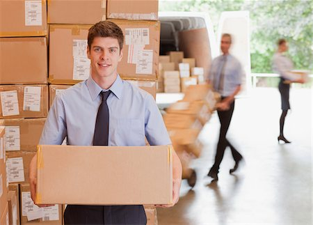 Businessman holding box in warehouse Stock Photo - Premium Royalty-Free, Code: 635-05651588