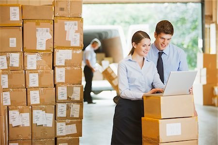 Business people using laptop in warehouse Stock Photo - Premium Royalty-Free, Code: 635-05651595