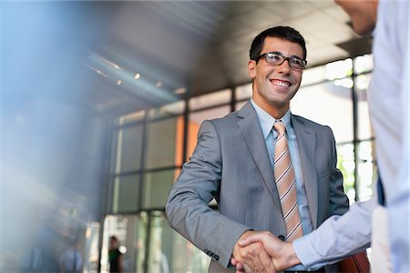 Businessmen shaking hands in office Stock Photo - Premium Royalty-Free, Code: 635-05651647