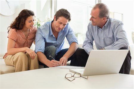 Couple signing papers with financial advisor Stock Photo - Premium Royalty-Free, Code: 635-05651848