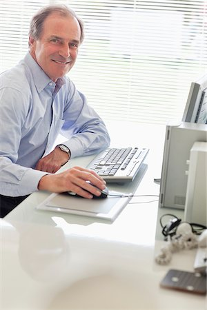 Businessman sitting at desk using laptop Stock Photo - Premium Royalty-Free, Code: 635-05651863