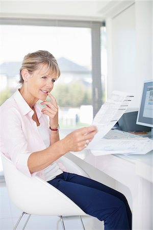 dubious - Woman looking at paperwork Stock Photo - Premium Royalty-Free, Code: 635-05651876