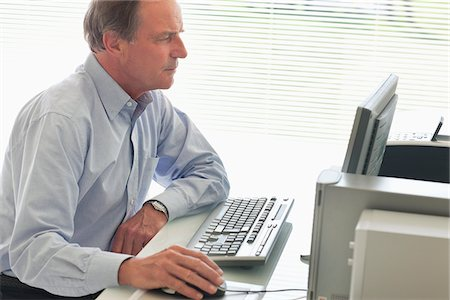 Businessman using computer at desk Stock Photo - Premium Royalty-Free, Code: 635-05651870