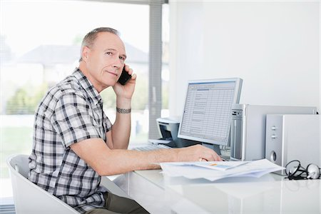 Man sitting at desk using cell phone Stock Photo - Premium Royalty-Free, Code: 635-05651885