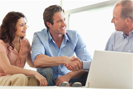 Couple shaking hands with financial advisor Stock Photo - Premium Royalty-Free, Code: 635-05651897