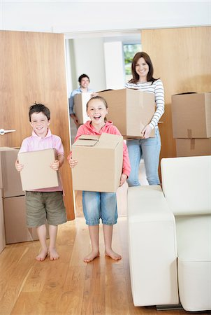 Family carrying moving boxes into new home Stock Photo - Premium Royalty-Free, Code: 635-05652111