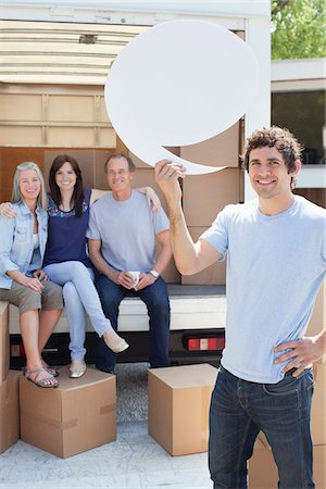 Friends unloading moving van, one man holding comment bubble Stock Photo - Premium Royalty-Free, Code: 635-05652139