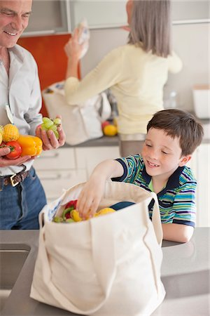 Boy helping to unload groceries from reusable bag Stock Photo - Premium Royalty-Free, Code: 635-05652225
