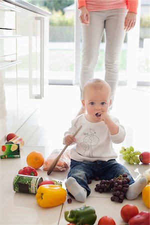 Baby making mess on floor with food Stock Photo - Premium Royalty-Free, Code: 635-05652239