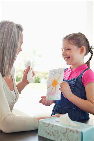 Granddaughter giving grandmother a get well soon card Stock Photo - Premium Royalty-Free, Code: 635-05652255