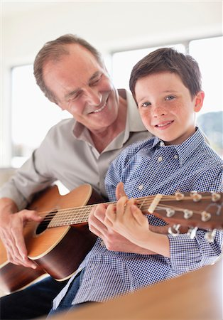 Grandfather teaching grandson to play guitar Stock Photo - Premium Royalty-Free, Code: 635-05652251
