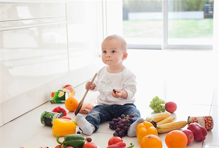 Baby making mess on floor with food Stock Photo - Premium Royalty-Free, Code: 635-05652267