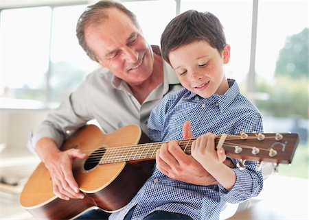 Grandfather teaching grandson to play the guitar Stock Photo - Premium Royalty-Free, Code: 635-05652269