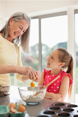 Grandmother and granddaughter baking cupcakes together Stock Photo - Premium Royalty-Free, Code: 635-05652278