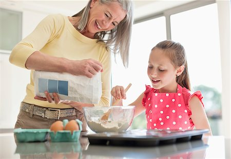 Grandmother and granddaughter baking cupcakes together Stock Photo - Premium Royalty-Free, Code: 635-05652285
