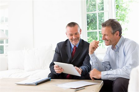 Financial advisor showing digital tablet to customer Stock Photo - Premium Royalty-Free, Code: 635-05652298