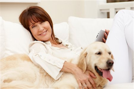 Woman sitting with dog on sofa using digital tablet Stock Photo - Premium Royalty-Free, Code: 635-05652315