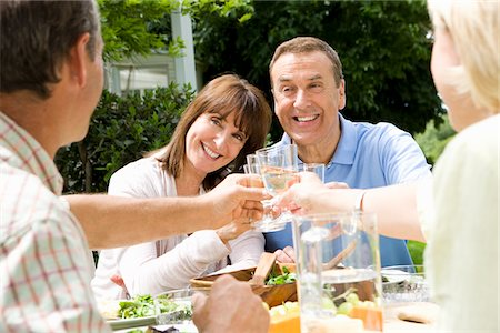 Friends toasting over lunch outdoors Stock Photo - Premium Royalty-Free, Code: 635-05652322