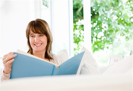 Woman sitting on sofa looking at photograph album Stock Photo - Premium Royalty-Free, Code: 635-05652333