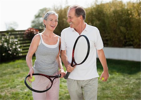 Couple outdoors holding tennis rackets Stock Photo - Premium Royalty-Free, Code: 635-05652389
