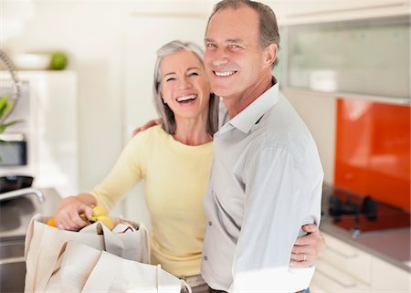 Smiling couple in kitchen with reusable grocery bags Stock Photo - Premium Royalty-Free, Code: 635-05652398