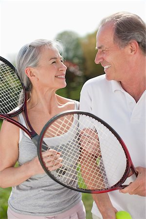Smiling couple holding tennis rackets Stock Photo - Premium Royalty-Free, Code: 635-05652409