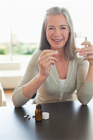 prevention - Smiling woman holding glass of water and taking pills Stock Photo - Premium Royalty-Free, Code: 635-05652421