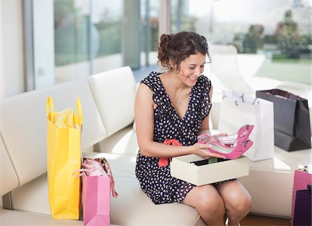 Excited woman taking shoes from box Stock Photo - Premium Royalty-Free, Code: 635-05652422
