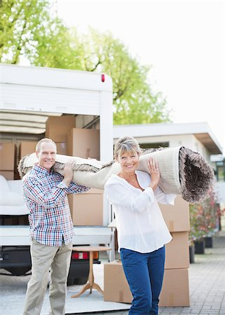 Couple carrying carpet from moving van Stock Photo - Premium Royalty-Free, Code: 635-05652432