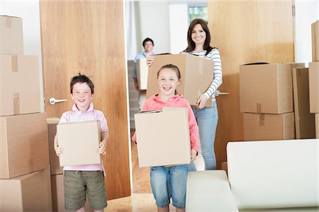 Family carrying boxes into new home Stock Photo - Premium Royalty-Free, Code: 635-05652433
