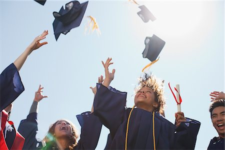 Graduates tossing caps into the air Stock Photo - Premium Royalty-Free, Code: 635-05971430
