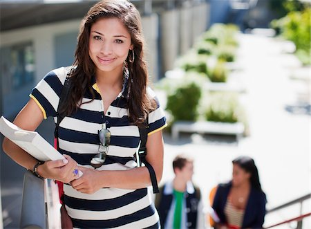 Student carrying book on steps outdoors Stock Photo - Premium Royalty-Free, Code: 635-05971474