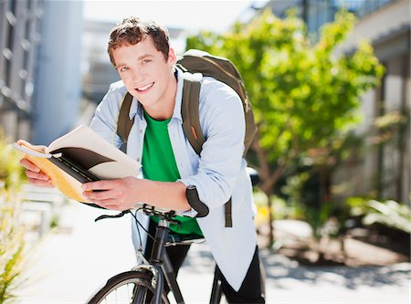 Student reading book on bicycle Stock Photo - Premium Royalty-Free, Code: 635-05971477