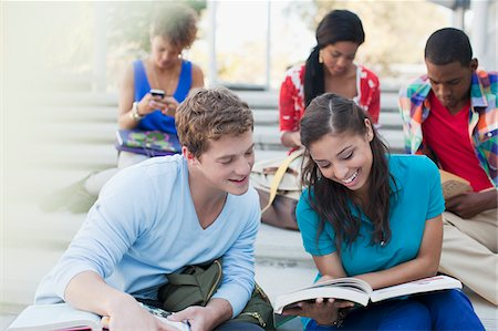 Students reading book together outdoors Stock Photo - Premium Royalty-Free, Code: 635-05971518
