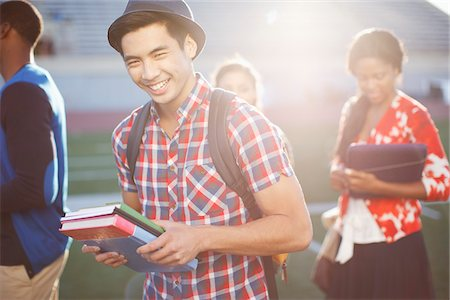 Student carrying books outdoors Stock Photo - Premium Royalty-Free, Code: 635-05971513