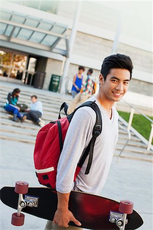 Student carrying skateboard outdoors Stock Photo - Premium Royalty-Free, Code: 635-05971529