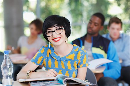 Student smiling at desk in classroom Stock Photo - Premium Royalty-Free, Code: 635-05971521