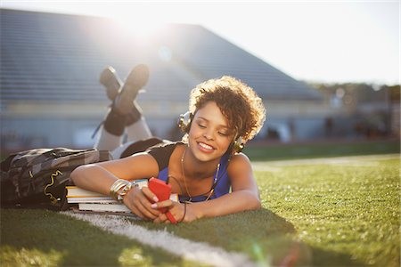 Student listening to mp3 player in grass Stock Photo - Premium Royalty-Free, Code: 635-05971537