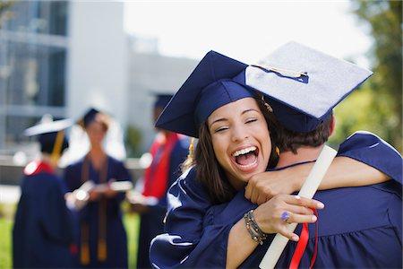 Smiling graduates hugging outdoors Stock Photo - Premium Royalty-Free, Code: 635-05971530