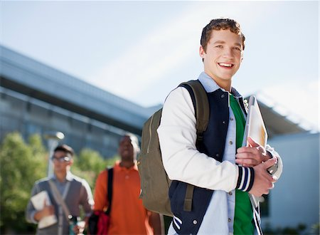 Student carrying folders outdoors Stock Photo - Premium Royalty-Free, Code: 635-05971546