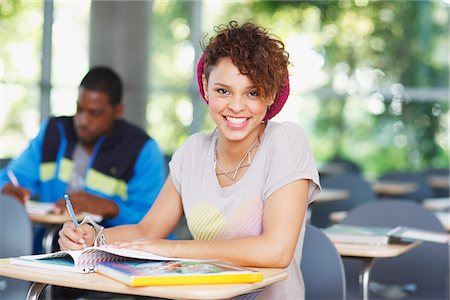 Student working at desk in classroom Stock Photo - Premium Royalty-Free, Code: 635-05971548